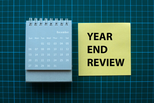 Top view of December calendar and yellow memo note written with Year End Review on green square background.