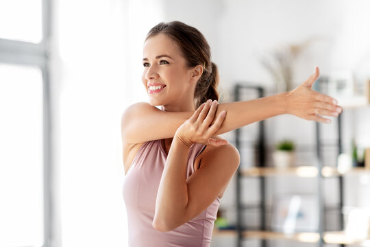 sport, fitness and healthy lifestyle concept - smiling young woman stretching arm at home