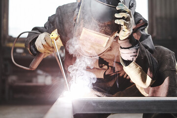 Man in protective mask welding metal construction.