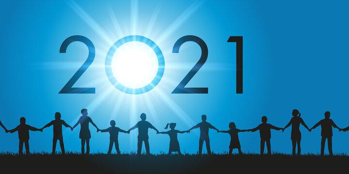 Un groupe d'hommes et de femmes de tous les âges ainsi que des enfants qui se donnent la main face au soleil et à l'année 2021 qui s'inscrit dans le ciel.