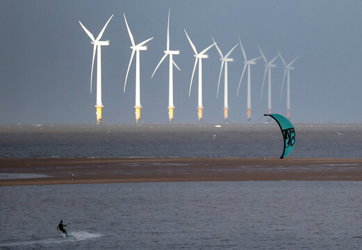 A kite surfer is pictured in front of the Burbo Bank offshore wind farm near New Brighton