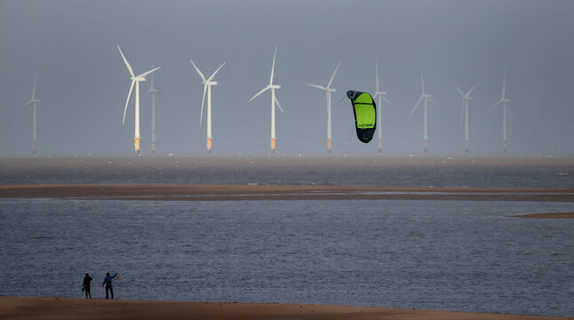 Kite surfers are pictured in front of the Burbo Bank offshore wind farm near New Brighton