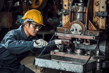 Asian engineer mechanic man checking and using wrench for maintenance pressing metal machine at...