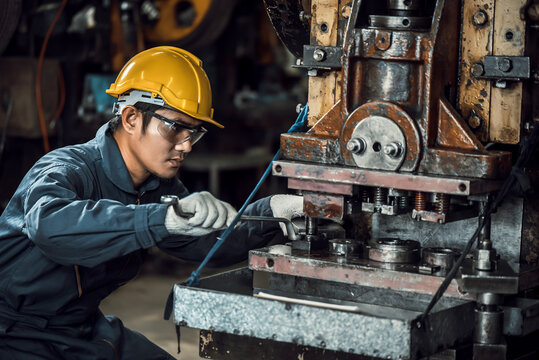 Asian engineer mechanic man checking and using wrench for maintenance pressing metal machine at factory, worker at industrial working concept