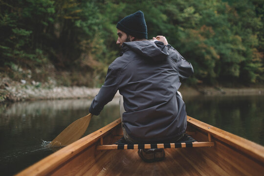 Autumn boat ride. Rear view of man paddling canoe on the forest lake
