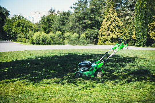 Electric lawn mower on a lawn at the garden.