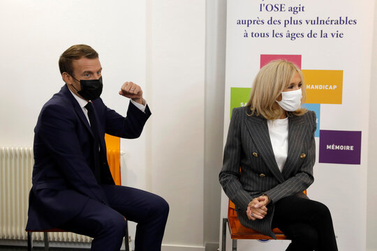 French President Emmanuel Macron and his wife Brigitte Macron talk to volunteers of the association OSE, which takes care of sick and disabled children in Paris