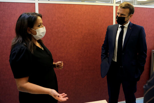French President Emmanuel Macron listens to a volunteer of the association OSE, which takes care of sick and disabled children in Paris