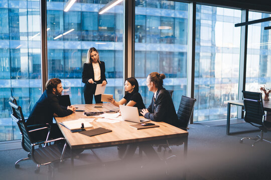 Diverse group of colleagues working on project together in boardroom