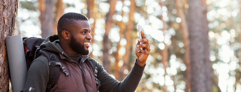 African man backpacker with smartphone in forest