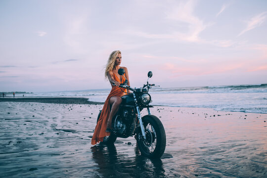 Young woman on motorcycle looking away on beach