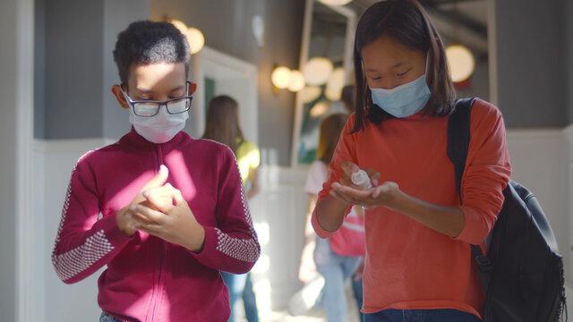 Multiethnic schoolchildren in safety mask disinfecting hands with sanitizer