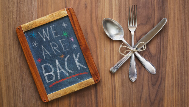 Restaurant blackboard announcing reopening after the corona lockdown,cutlery and blackboard,food business restart concept with message we are back