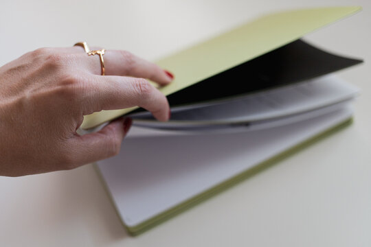 Woman hand with red nails and gold rings opening a green notebook