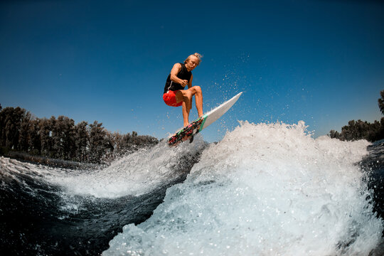 view of athletic man on surf style wakeboard jumping over splashing wave