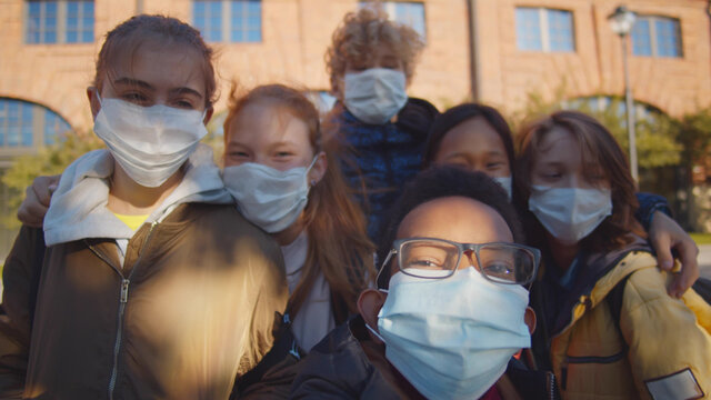 Multiethnic school children wearing protective face masks taking selfie outdoors