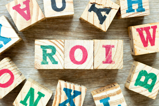 Alphabet letter block in word ROI (Abbreviation of Return on Investment) with another on wood background