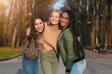 Trio of pretty teen girls posing in public park