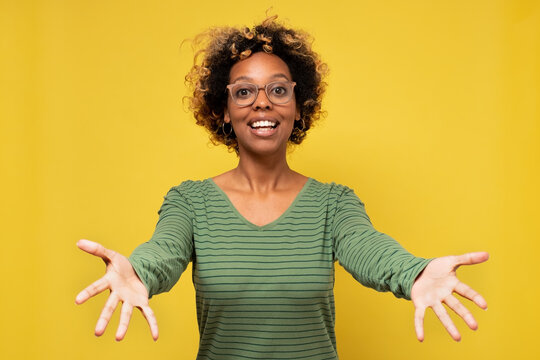 Young african american woman smiling with open arms for hug welcoming her friends