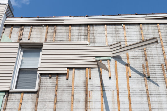 White Home Building Exterior during a Renovation with Wood Siding