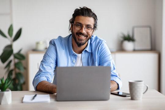 Happy Indian Freelancer Man Sitting At Desk With Laptop, Smiling At Camera