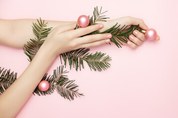 Close up beautiful womans hands holding a Christmas tree branch with pink balls on the pink...
