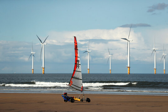 Wind turbines are seen in the background as a person practices land yachting at Redcar Beach in Redcar