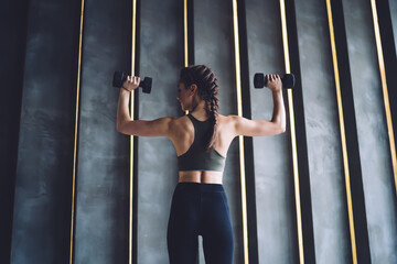 Strong woman exercising with dumbbells