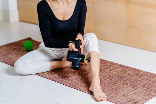 Lifestyle shot of unrecognizable female practicing self-massage technique for legs applying therapeutic percussive massage gun sitting on pilates mat at home or studio interior.