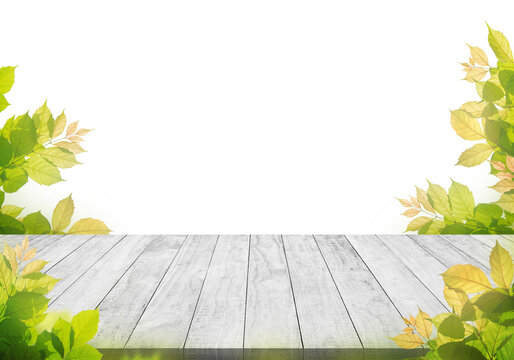 white wooden table top with spring green leafs as frame and free space for text..