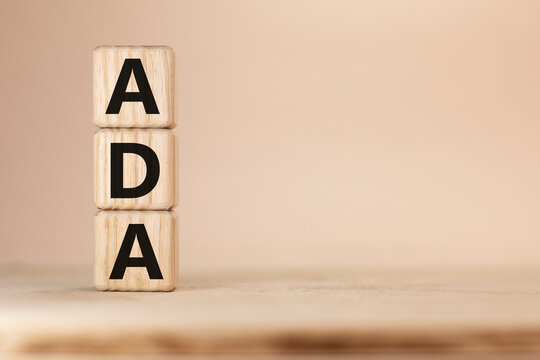 Word ADA Americans with Disabilities Acton wooden blocks beige background top view