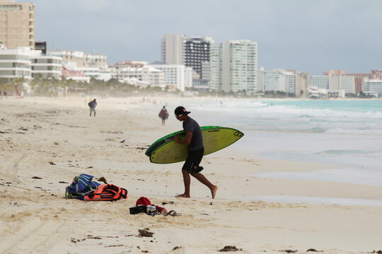 A man removes surf boards from a beach in preparation for the arrival of Hurricane Delta, in Cancun