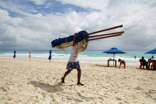 A hotel employee removes beach umbrellas from a beach in preparation for the arrival of Hurricane Delta, in Cancun
