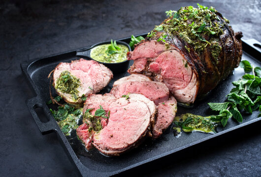 Traditional English barbecue lamb roast sliced with mint leaf and sauce offered as close-up in a design cast-iron tray