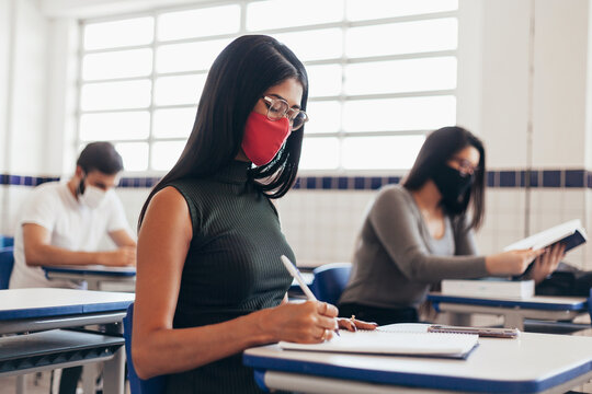 Brazilian college students wearing face masks sitting at the desk in the classroom. Concept of reopening of educational institutions in the COVID-19 pandemic