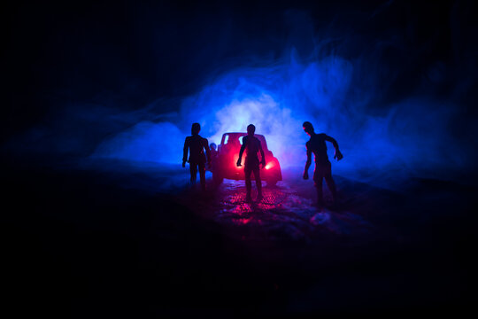 photo of a car stopped on the road lighting up a zombies. Silhouette terrible zombie night near the car. Miniature decoration.