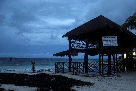 A man takes a video with his phone at a beach as Hurricane Delta approaches Cancun