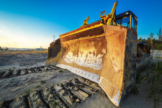 Tracked tractor with large sand clearing bucket.