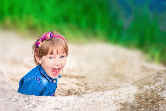 Joyful child with an open mouth in denim suit plays in the sand on the river bank.