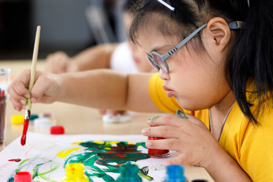 Asian girl with Down's syndrome painting in art class.
