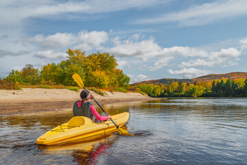 Kayak fun water sports down on river in Laurentians, Quebec. Canada travel destination. Woman kayaker kayaking in Mont-Tremblant during autumn.