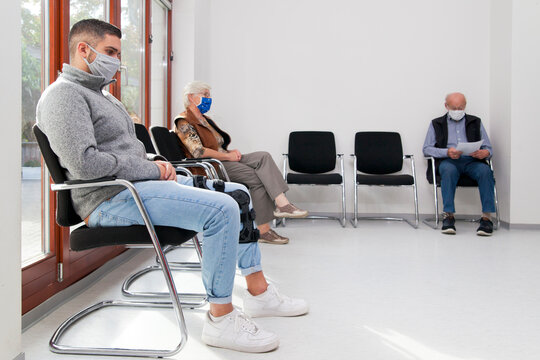Young and old people with face masks keeping social distance in a waiting room of a hospital or office