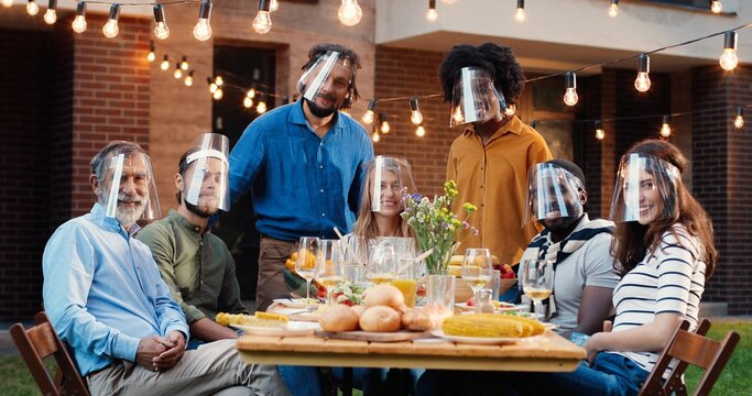 Portrait of mixed-races people in face shields at dinner table in back yard and smiling to camera. Multi ethnic family at picnic in court outdoors. Pandemic communication of generations.