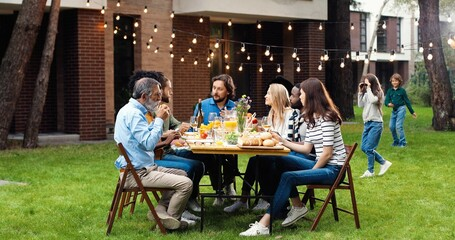 Happy Caucasian family sitting at table with meal outdoor at picnic and talking. Joyful young and old people having dinner and having nice communication. Weekend celebration gathering.