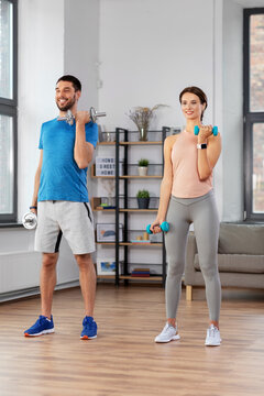 sport, fitness, lifestyle and people concept - smiling man and woman exercising with dumbbells at home