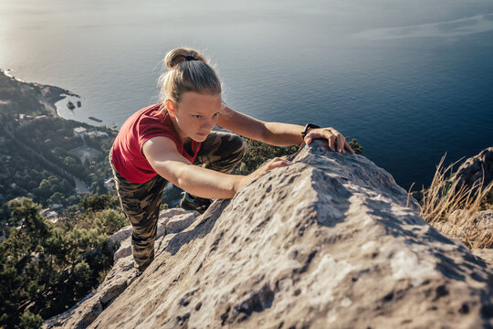 Young strong girl climbs to top of cliff. Overcoming obstacles and courage. Ambitious climber climbing high mountain to achieve success