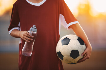 Soccer Boy in Jersey Shirt Holding Water Bottle and Soccer Ball. Sporty Child in Soccer Clothes on a Sunny Morning Training. Junior Football Activity Background