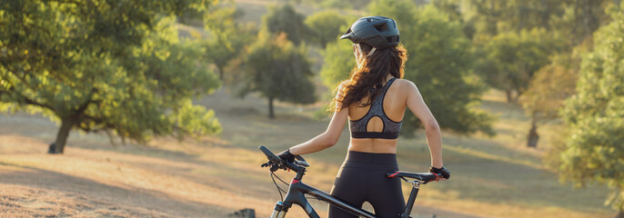Young female cyclist cycling on rural road, side view.