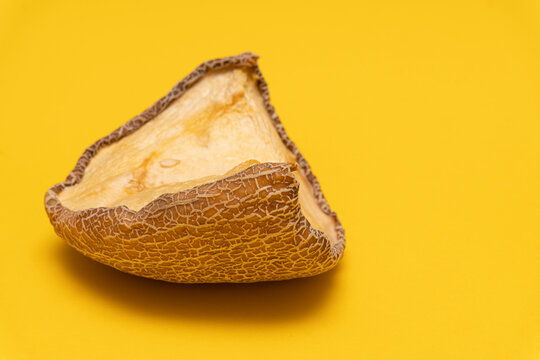 View at moldy dried melon at yellow background, copy space, spoiled product, closeup, not edible