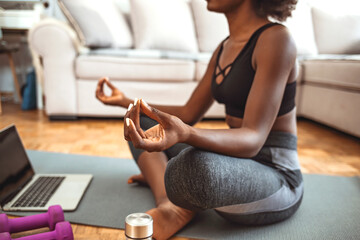 Shot of an attractive young woman practicing yoga at home. Shot of a fit young woman meditating at home. African-American woman meditating in lotus position. Making time to meditate